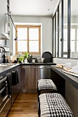 Stainless steel cabinets and bar stools in narrow kitchen