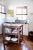 Country kitchen with wooden floor, sink and kitchen worktop on a wooden table with storage space