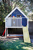 Elevated play house with slide and sandpit in the garden