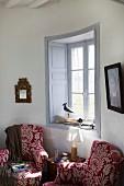 Armlehnsessel mit rot-weißem Ornamentmuster vor Sprossenfenster
