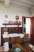 Kitchen sink unit with wooden base cabinet against red- brown tiled splashback