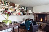 Antiker Konsolentisch unter Wandboards mit Büchern und Armlehnsessel vor offenem Kaminfeuer