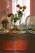 Table autumnally decorated with roses, bunches of berries and artichokes