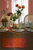 Herbstlich gedeckter Tisch dekoriert mit Rosen, Beeresträussen und Artischocken