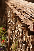 Stack of firewood topped with roof tiles