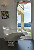 Sculptural designer chaise in front of glass door