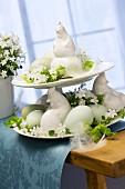 Etagere mit Hühnerfiguren aus Keramik, Ostereiern, weissen Glockenblumen und Birkengrün