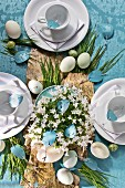 Easter table set with birch bark and blades of grass on blue wallpaper