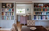 View from dining room with bookcases into rustic kitchen with pastel panelled cabinets