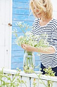 Woman wearing striped top arranging flowers in preserving jar