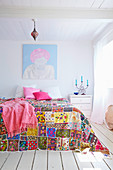 Brightly embroidered bedspread on bed in white bedroom