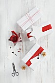 Gifts wrapped in red and white and wrapping materials