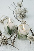 Windlicht aus Eis und eingefrorenen Blättern zwischen Zweigen mit Flechten