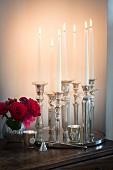 Ein Tablett mit vielen silbernen Kerzenständern und brennenden Kerzen, ein Rosensträußchen