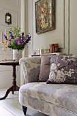 Floral scatter cushions on floral sofa in front of vase of flowers and floral painting