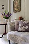 Geblümtes Sofa mit Blumenkisten, dahinter Vase mit Blumenstrauß und ein Blumen-Gemälde