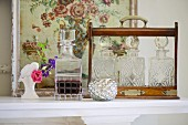Cut-glass carafes in wooden bottle carrier in front of antique floral picture
