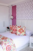 Bed with upholstered headboard and colourful scatter cushions against purple-patterned wallpaper