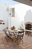 Masonry barbecue and metal table and chairs in Mediterranean courtyard