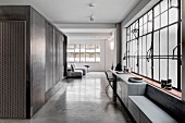 Industrial loft apartment in shades of grey with concrete floor and factory windows