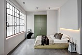 Schlafzimmer im Industrie-Loft mit Estrichboden und Fabrikfenstern