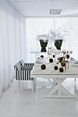 Modern table set for Christmas meal with artificial snow, moss balls and stag candelabra