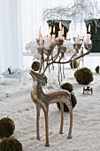 Silver candelabra in shape of a stag with lit candles on antlers stodd amongst artificial snow