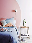 Modern bedroom with a pink circle painted on the wall as the head of the bed