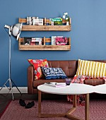 Bookshelf made of sawn-up pallets on a blue wall above a leather sofa