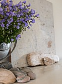 Campanula in silver urn next to stone tile and pebbles