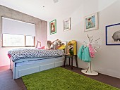 Girl with dog on bed in children's room with concrete wall and flea market items