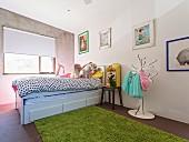 Mädchen mit Hund auf Bett im Kinderzimmer mit Betonwand und Flohmarktartikeln