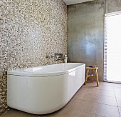Freestanding, white bathtub on mosaic tile wall in minimalist bathroom with concrete wall