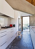 View of white designer fitted kitchen units and massive concrete beams, garden view