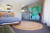 Open bedroom with large, modern picture on concrete wall