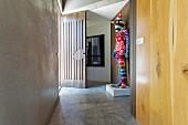 Colorfully crocheted artificial figure in the entrance area with concrete floor and concrete wall