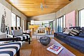 Offener Loungebereich mit Blick auf Essbereich und Küchenzeile in Architektenhaus mit Betonwänden, Holzdecke und modernen Kunstbildern