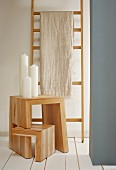 Linen cloth hung over wooden ladder used as clothes rack and pillar candles on adjustable wooden stool