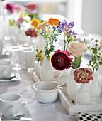 Gedeckter Tisch mit weißem Geschirr und Frühlingsblumen