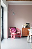Pinker Korbsessel und Retro-Kommode vor rosafarbener Wand