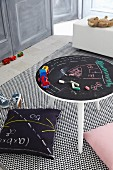 Games table with drawings on chalkboard top on rug with graphic pattern
