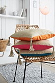 Stacked cushions with hand-sewn covers and tassels on wicker chair