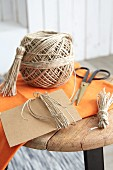 Parcel string, cardboard and scissors for making tassels