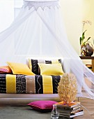 Colourful cushions on ethnic-style couch below canopy