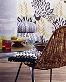 Zigzag-patterned cushion on wicker chair in front of patterned wall
