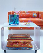 Colourful cushions with crocheted trim inside white metal coffee table in front of bright orange, floral sofa