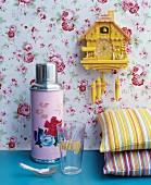 Pink thermos flask with floral motif next to brightly striped cushions below yellow cuckoo clock on rose-patterned wallpaper