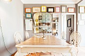 Antique dining table and white metal chairs inn front of gallery of pictures and mirrors on grey wall