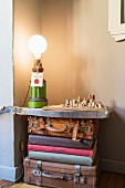 Table lamp and architectural model on surface on top of stacked vintage suitcases and books