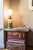 Vintage Koffer und Bücher unter Ablage mit Tischleuchte und Architekturmodell in Zimmerecke